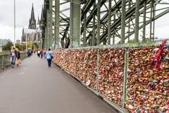 COLOGNE TYSKLAND - AUGUSTI 26, 2014, tusentals förälskelselås som älsklingar låser till den Hohenzollern bron för att symbolisera Arkivfoto