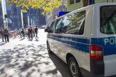 COLOGNE TYSKLAND, OKTOBER 2018: Polisbil och folk som framme går i fyrkanten av huset för Cologne ` s arkivbild