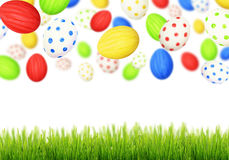 Cololrful Easter eggs falling at green grass Stock Images
