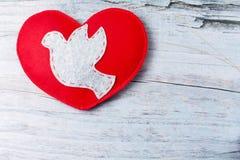 Colombe grise sentie, coeur fabriqué à la main rouge sur le fond en bois Photographie stock libre de droits