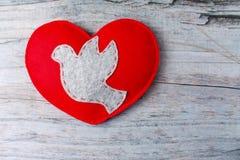 Colombe grise sentie, coeur fabriqué à la main rouge sur le fond en bois Photographie stock