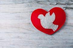 Colombe grise sentie, coeur fabriqué à la main rouge sur le fond en bois Photos stock