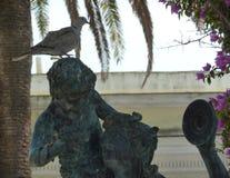 Colombe se reposant sur la tête d'une statue du grec ancien photographie stock