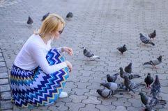 Colombes de groupe sur les festins de attente de place de ville Générosité de part Place de ville de détente de femme blonde de f photographie stock libre de droits