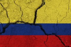 Colombia flag on the cracked earth. National flag of Colombia. Earthquake or drought concept stock photo