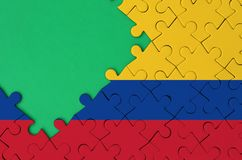 Colombia flag is depicted on a completed jigsaw puzzle with free green copy space on the left side.  royalty free illustration