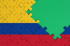 Colombia flag is depicted on a completed jigsaw puzzle with free green copy space on the right side.  stock illustration
