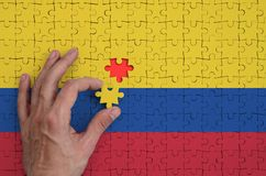 Colombia flag is depicted on a puzzle, which the man`s hand completes to fold.  stock illustration