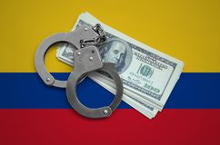 Colombia flag with handcuffs and a bundle of dollars. Currency corruption in the country. Financial crimes.  stock photography