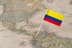 Colombia flag pin on world map. Paper flag pin of Columbia on a world map showing neighboring countries. Officially the Republic of Columbia, it is a sovereign stock photo