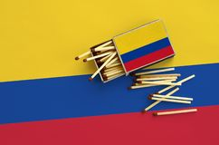 Colombia flag is shown on an open matchbox, from which several matches fall and lies on a large flag.  royalty free stock photo