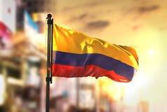 Colombia flagga mot suddig bakgrund för stad på soluppgång Backlig Royaltyfri Foto