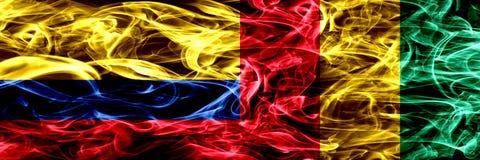 Colombia versus Guinea, Guinese zij aan zij geplaatste rookvlaggen Dik gekleurde zijdeachtige Guinese rookvlaggen van Columbiaans royalty-vrije illustratie
