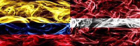 Colombia versus Letland, Letse zij aan zij geplaatste rookvlaggen Dik gekleurde zijdeachtige Letse rookvlaggen van Columbiaans en royalty-vrije illustratie
