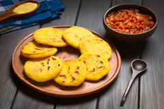 Colombian Arepa with Hogao Sauce. Arepas with Colombian hogao sauce (tomato and onion cooked) in the back. Arepas are made of yellow or white corn meal and are Royalty Free Stock Photo