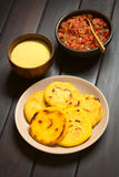 Colombian Arepa with Hogao Sauce. Plate of arepas with Colombian hogao sauce (tomato and onion cooked) and corn meal in the back. Arepas are made of yellow or Stock Image