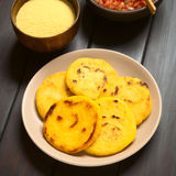 Colombian Arepa. Plate of arepas with Colombian hogao sauce (tomato and onion cooked) and corn meal in the back. Arepas are made of yellow or white corn meal and Royalty Free Stock Image
