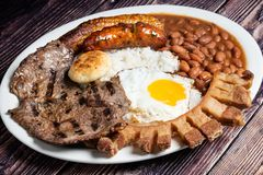 Colombian Bandeja Paisa. From above over a wooden table royalty free stock photo