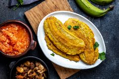 COLOMBIAN CARIBBEAN CENTRAL AMERICAN FOOD. Patacon or toston, fried and flattened whole green plantain banana on white. Plate. Black background, top view stock photography