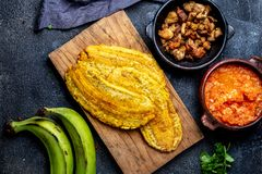 COLOMBIAN CARIBBEAN CENTRAL AMERICAN FOOD. Patacon or toston, fried and flattened whole green plantain banana on white. Plate. Black background, top view royalty free stock photo