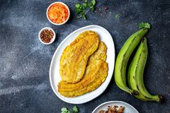 COLOMBIAN CARIBBEAN CENTRAL AMERICAN FOOD. Patacon or toston, fried and flattened whole green plantain banana on white. Plate. Black background, top view royalty free stock photography