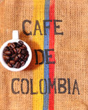 Colombian coffee. Roasted coffee beans on top of a rugged carpet painted with the Colombian flag colors Stock Image