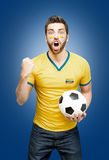 Colombian fan holding a soccer ball celebrates on blue background.  Royalty Free Stock Images