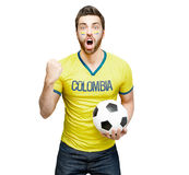 Colombian fan holding a soccer ball celebrates on white background.  Stock Photography