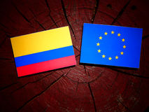 Colombian flag with EU flag on a tree stump isolated. Colombian flag with EU flag on a tree stump Stock Photo