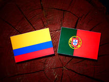 Colombian flag with Portuguese flag on a tree stump isolated. Colombian flag with Portuguese flag on a tree stump stock illustration
