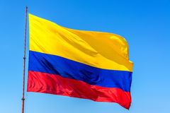 Colombian Flag. Resplendent Colombian flag waving in the wind set against a beautiful blue sky Royalty Free Stock Images