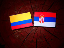 Colombian flag with Serbian flag on a tree stump isolated. Colombian flag with Serbian flag on a tree stump royalty free stock image
