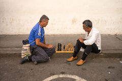Colombian men playing chess on the sidewalk Royalty Free Stock Photography