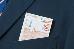 Colombian Pesos in the pocket of a suit. Background Stock Photos