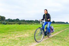 Colombian woman cycling on path in dutch nature landscape Stock Photo