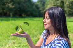 Colombian woman looking at pear on hand outside Royalty Free Stock Photo