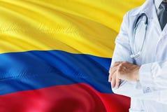 Colombianskt doktorsanseende med stetoskopet på Colombia flaggabakgrund Nationellt v?rdsystembegrepp, medicinskt tema royaltyfri bild