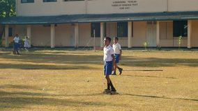 Concentrated Sinhalese schoolboys play cricket. Colombo/SRI LANKA - APRIL 05 2019: Concentrated Sinhalese schoolboys play cricket on playground with trees stock video