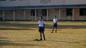 Sinhalese boys on playground against school building. Colombo/Sri Lanka - April 05 2019: Sinhalese boys in blue shorts and white shirts stand on playground stock footage