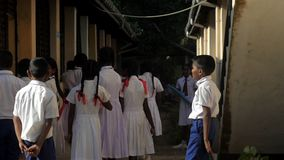 Boys and girls gather at school building lit by sun. Colombo/SRI LANKA - APRIL 05 2019: Sinhalese boys and girls gather at school building lit by bright autumn stock video