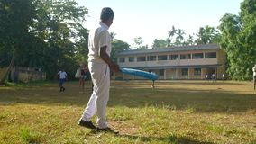 Sinhalese schoolboy plays cricket on playground. Colombo/Sri Lanka - April 05 2019: Sinhalese schoolboy in white uniform plays cricket on green playground slow stock footage