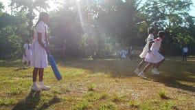 Sinhalese schoolgirls play cricket on playground. Colombo/SRI LANKA - APRIL 05 2019: Sinhalese schoolgirls play cricket on playground with trees shadows at stock footage