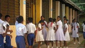 Sinhalese schoolkids stand waiting for lesson in school yard. Colombo/SRI LANKA - APRIL 05 2019: Sinhalese schoolkids in uniforms stand at building in school stock video