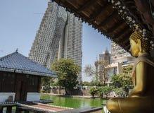 Colombo, Sri Lanka - April 1,2019: Sitzender Buddha im Seema Malaka-Tempel mit den Skylinen im Hintergrund lizenzfreie stockbilder