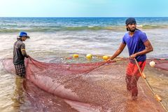 Two fishermen get from the sea to the shore a trawl with fish on a sunny day. Colombo, Sri Lanka - January 14, 2018. Two fishermen get from the sea to the shore royalty free stock image