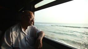 COLOMBO, SRI LANKA - MÄRZ 2014: Älterer Mann, der heraus das Fenster des Zugs schaut Die Schienentransportmillionen Sri Lankan vo stock video footage