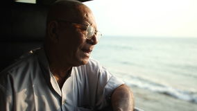 COLOMBO, SRI LANKA - MÄRZ 2014: Älterer Mann, der heraus das Fenster des Zugs schaut Die Schienentransportmillionen Sri Lankan vo stock video