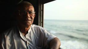 COLOMBO, SRI LANKA - MARCH 2014: Elderly man looking out the window of train. The Sri Lankan railway transports millions of people stock video