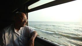 COLOMBO, SRI LANKA - MARCH 2014: Elderly man looking out the window of train. The Sri Lankan railway transports millions of people stock video footage
