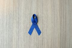 Colon Cancer Awareness, dark blue Ribbon on wooden background for supporting people living stock photography